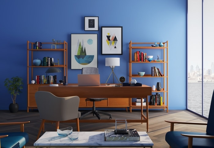 Landscape styled picture of an office space. There is a big panoramic window on the right wall of the picture. A wooden desk sits in the center of the room with matching wooden bookshelves behind it. Each bookshelf is lined with mid-century modern decor. There is a waist high plant in the left corner of the room. The entire room is painted a deep ocean blue.