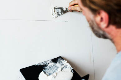 An up-close image of a am doing drywall repair to fix a whole in a wall with paint. The wall is white and the man is facing the wall where we can't see his face.
