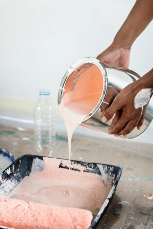 A personas hands are in a close up view pouring a silver gallon sized bucket of paint into a pan to be rolled onto a wall. The paint being poured is pink, and the floor underneath is layered with cardboard to protect it.